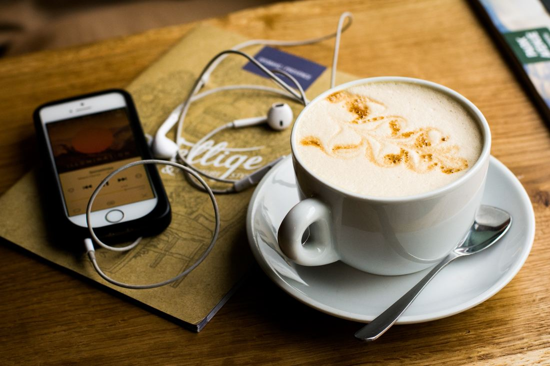 Cup of coffee with iphone and headphones